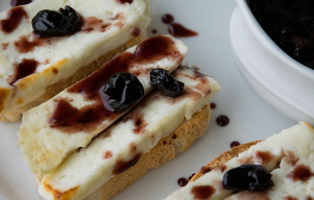 Image of cheese slivers over crispy baguette slices and wild cherry jam from Clay's Lebanese Mezza menu