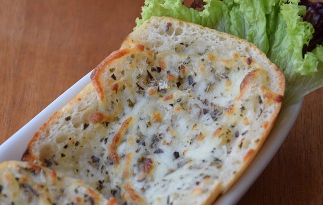 Image of toasted garlic bread with melted cheese and oregano from Clay restaurant's appetizer menu