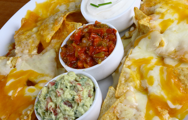 Image of tortilla chips with melted cheddar and mozzarella cheese, served with guacamole, marinara sauce, and sour cream.